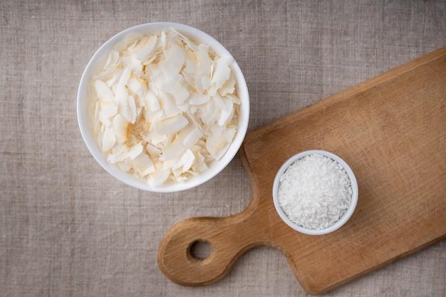 Lascas e lascas de coco em uma tigela sobre uma toalha de mesa e tábua de cortar