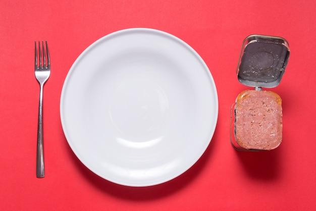 Lata aberta com carne em lata, mesa da cozinha com vista superior