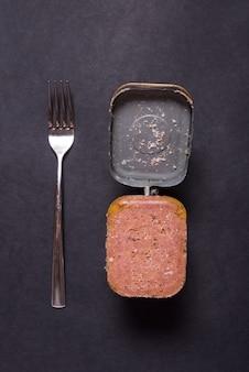 Lata aberta com carne em lata, vista superior fundo preto