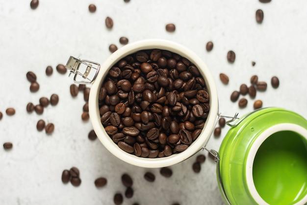 Lata aberta com grãos de café e grãos de café estão espalhados em um espaço de concreto. bandeira. conceito de café fresco