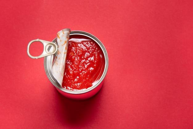 Lata aberta com tomates enlatados, sobre fundo vermelho