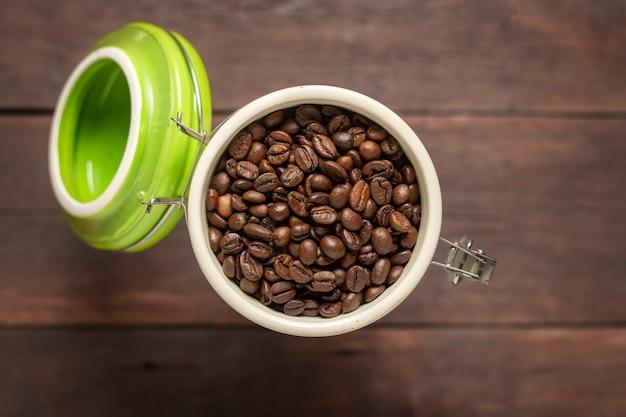 Lata com grãos de café em uma mesa de madeira.
