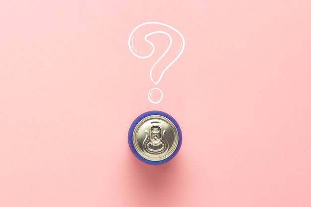 Lata com uma bebida em um fundo rosa com um ponto de interrogação. minimalismo. conceito de uma bebida desconhecida, tente pela primeira vez vista plana, vista superior.
