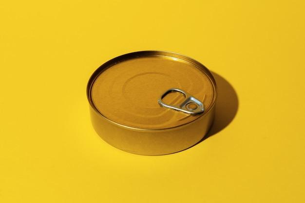 Lata de comida enlatada no fundo amarelo do estúdio