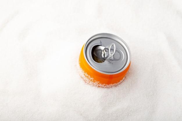 Lata de laranja de refrigerante gaseificado e pilha de açúcar excesso de açúcar em refrigerantes e refrigerantes