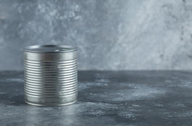 Lata de lata de metal colocada sobre mármore.