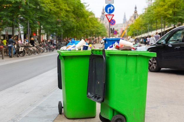 Lata de lixo verde na calçada, cidade europeia. caixa de lixo cheia na rua da europa, ninguém, lata de lixo, grande lixeira de plástico ao ar livre
