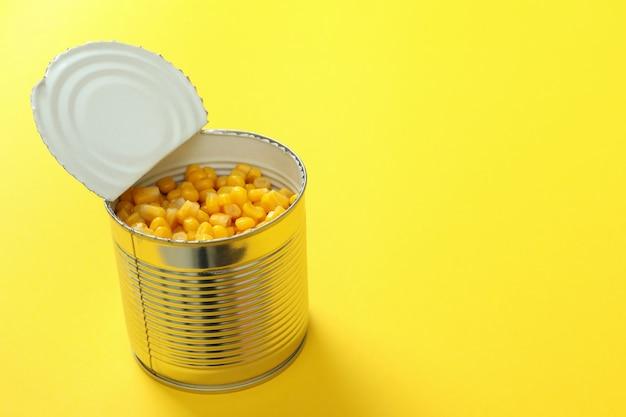 Lata de milho enlatado na parede amarela, espaço para texto