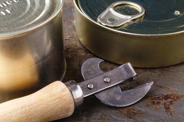 Lata de peixe com abridor de lata na mesa de madeira