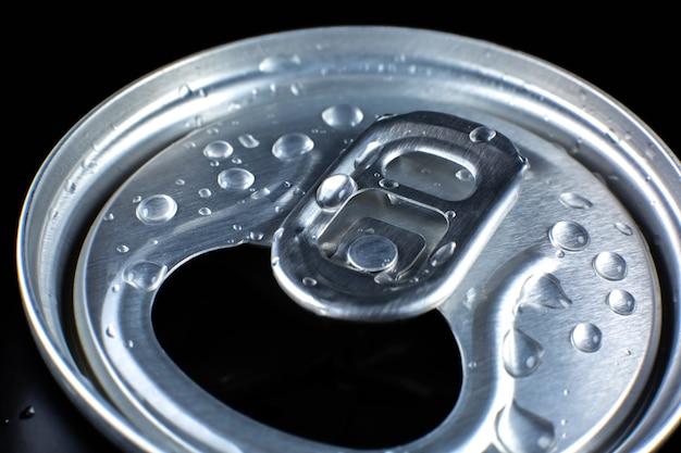 Lata de refrigerante com gotas em fundo preto. refrescante durante o calor do verão. humor de férias.