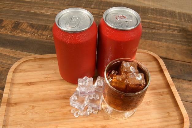 Lata de refrigerante com um copo cheio de gelo e bebida na bandeja de bambu