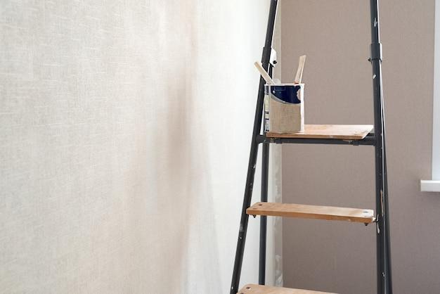 Lata de tinta com pincéis na escada