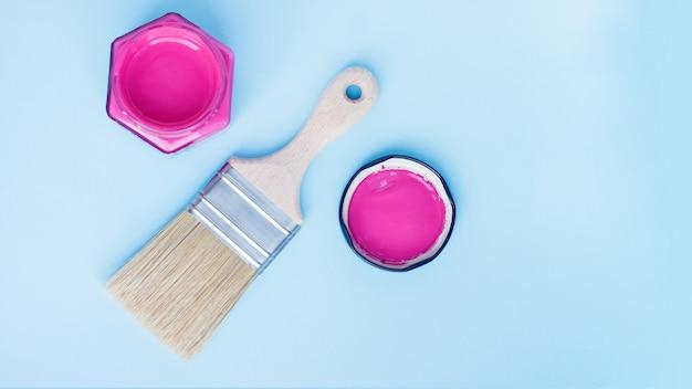 Lata de tinta com tinta roxa e pincel novo sobre fundo azul. renovação da casa. passatempo. terapia de cores.