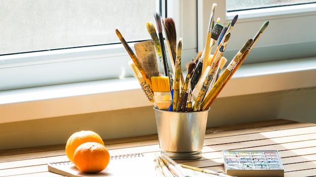 Lata metálica com escovas em uma mesa