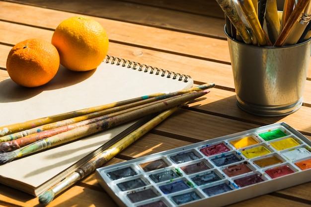 Lata metálica com pincéis com aquarela e notebook em uma tabela