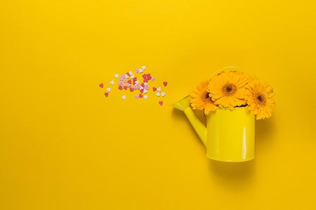 Lata molhando amarela com flores e corações confetti