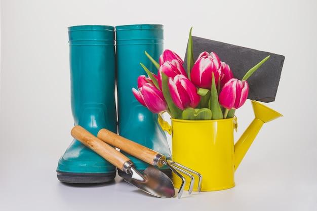 Lata molhando com flores e itens de jardinagem