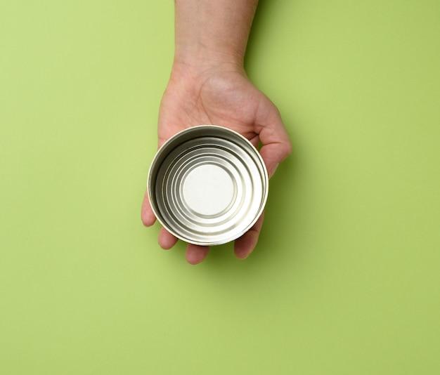 Lata redonda de metal aberta em uma mão feminina em um fundo verde, vista superior
