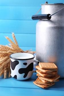 Lata retrô para leite, leite no copo, biscoito e molho na mesa de madeira colorida