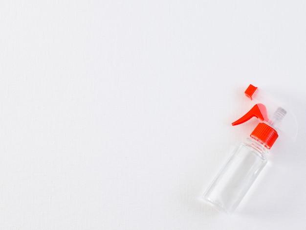 Lata transparente cheia de desinfecção de álcool contra infecção por covid-19 em uma mesa branca