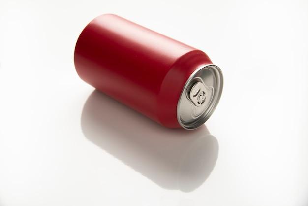 Lata vermelha de fundo reflexo branco de refrigerante.