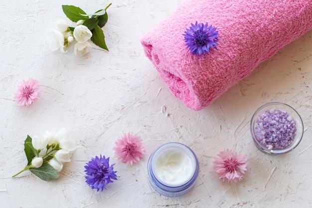Latas com sal marinho e creme para a pele, toalha e flores de jasmim e centáurea em um fundo branco. produtos femininos para spa. vista do topo.