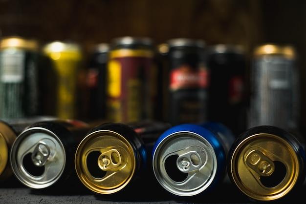 Latas de cerveja vazias coloridas sobre um fundo escuro