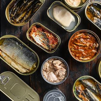 Latas de conservas com diferentes tipos de peixes e frutos do mar, sobre tábuas rústicas de madeira escura