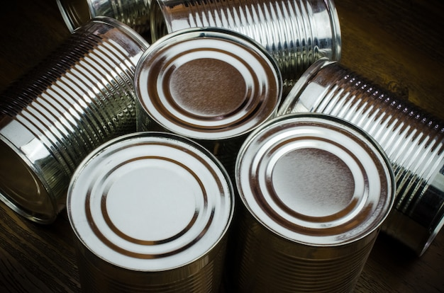 Latas de lata para o alimento no fundo de madeira.