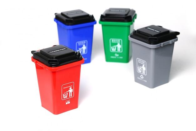 Latas de lixo de plástico coloridas isoladas no branco