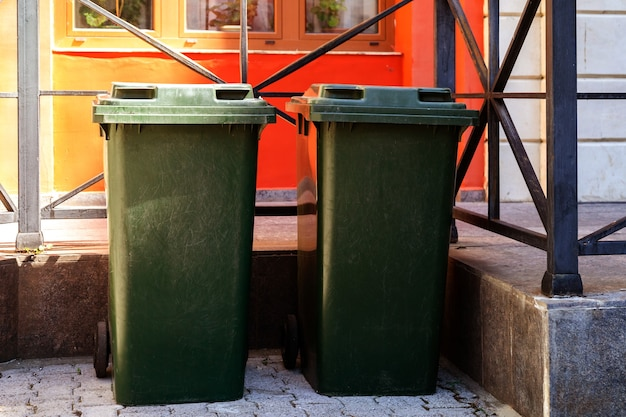 Latas de lixo verdes na frente da casa