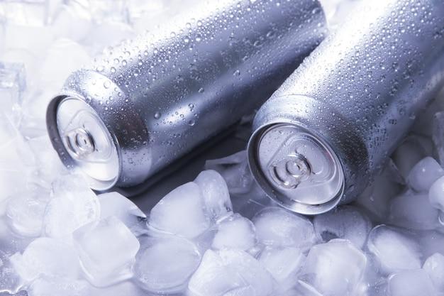 Latas de metal de cerveja com cubos de gelo, close-up