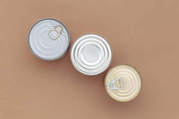Latas de metal de comida enlatada em um fundo marrom. vista do topo