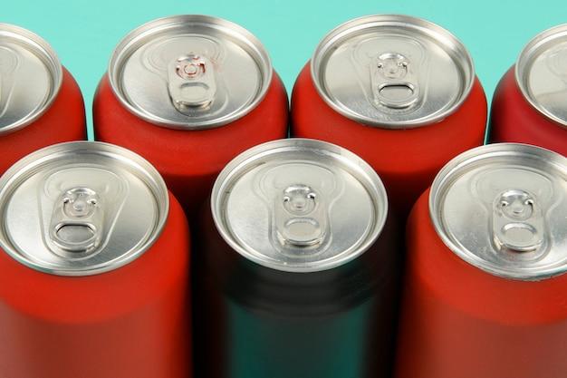 Latas de refrigerante vermelhas alinhadas vistas de cima com uma lata preta misturada