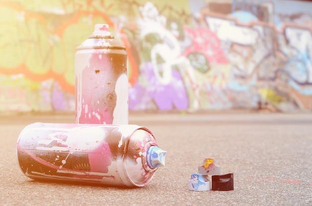 Latas de spray usadas com tinta rosa e branca e tampas para tinta spray