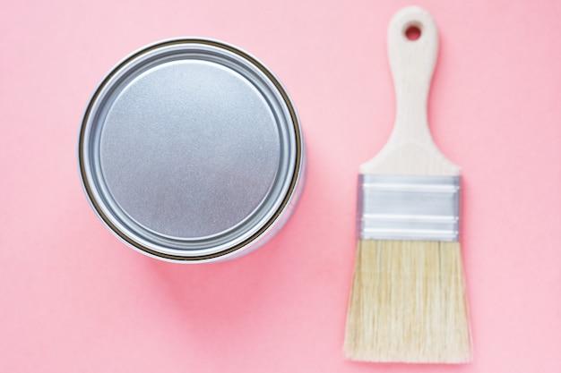 Latas de tinta e pincel novo em fundo rosa. concentre-se no pincel. renovação da casa. passatempo. terapia de cores