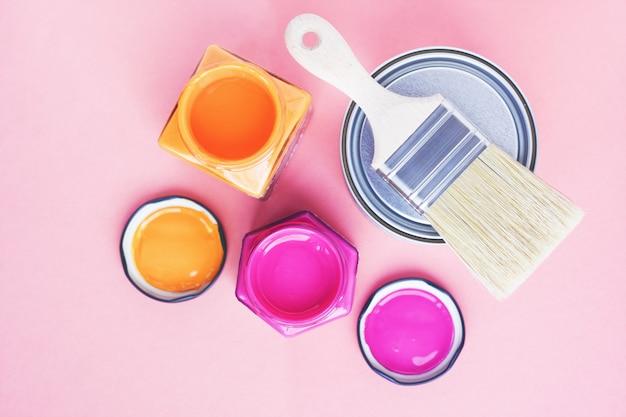 Latas de tinta e pincel novo em fundo rosa. concentre-se no pincel. renovação da casa. terapia de cores