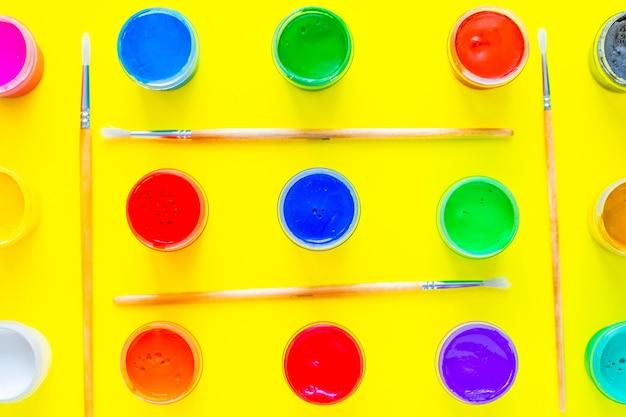 Latas de tinta multicolorida por toda a imagem, suas fileiras são separadas por pincéis sobre um fundo amarelo ...