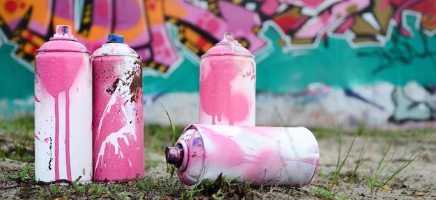 Latas de tinta usadas ficam no chão perto da parede com uma bela pintura de grafite