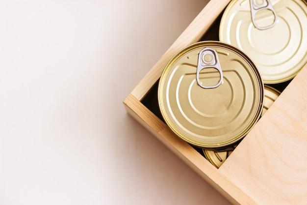 Latas em uma caixa. uma variedade de comida enlatada em latas cheias. comida enlatada de verdade. vista de cima. foco seletivo.