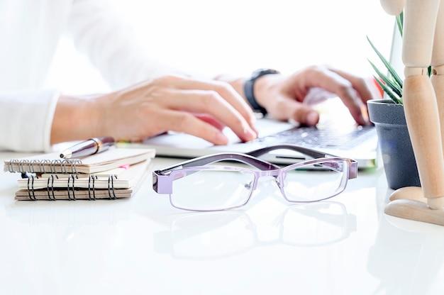 Lateral da mesa de escritório branca com óculos e desfocar a imagem homem mão digitando no laptop.