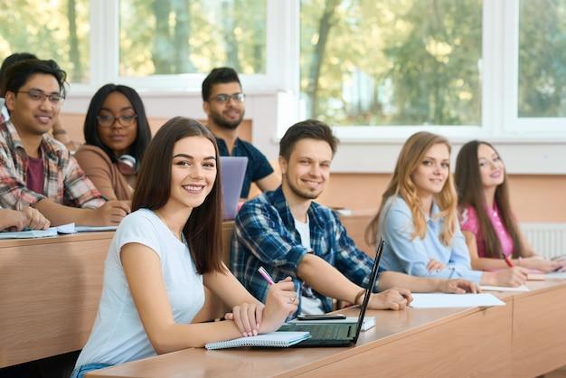 Lateral de groupmates olhando para a câmera durante a aula.