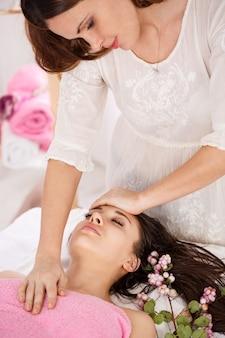 Lateral do jovem massagista fazendo massagem facial na jovem mulher