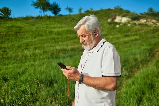 Lateral do velho olhando para o celular ao ar livre.