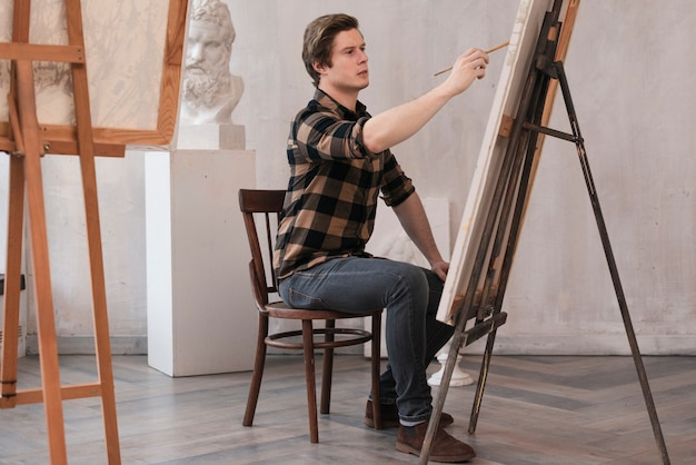 Lateralmente artesão homem pintura sobre tela