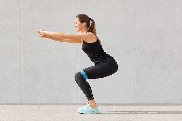 Lateralmente desportiva jovem europeia tem treino com elástico, vestido com roupas esportivas pretas, tem exercícios para nádegas, poses em cinza. conceito de motivação.