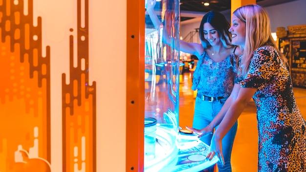 Lateralmente feliz mulheres jogando jogo de arcade