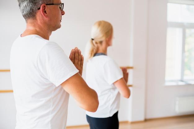 Lateralmente homem e mulher praticando ioga