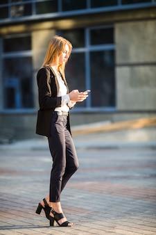 Lateralmente, mulher, caminhando, enquanto, usando, dela, telefone