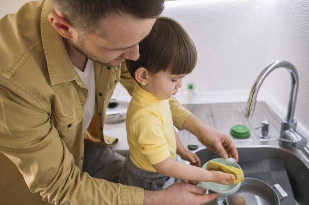 Lateralmente pai e filho lavando a louça